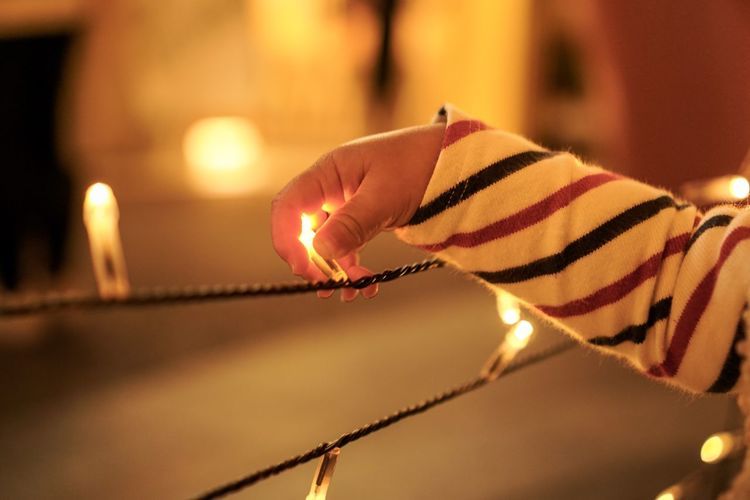 Cropped hand of baby holding illuminated string light at night