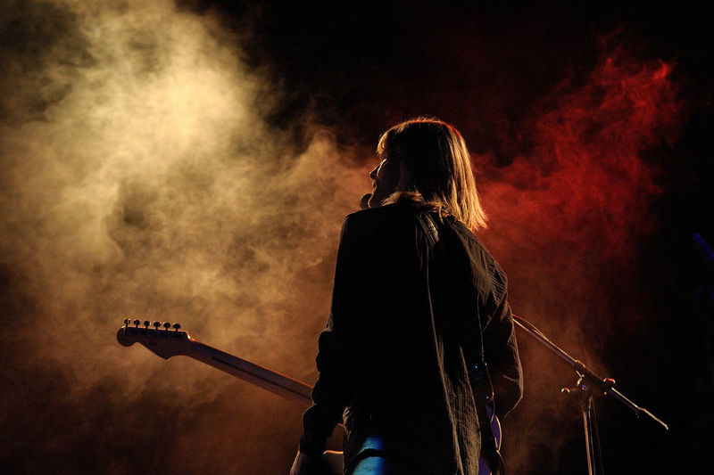 Rear view of man playing guitar at music concert