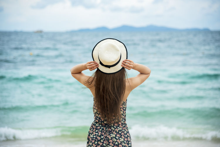 Woman wearing hat standing at beach