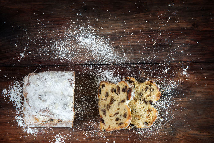 Christmas background, german criststollen cake sprinkled with powdered sugar on a dark rustic wooden board, top view from above, copy space Christmas Holiday Background Baked Cake Christstollen Day Food Food And Drink High Angle View Indoors  No People Sweet Food Table Traditional