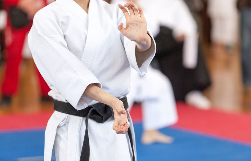 Midsection of man practicing karate on carpet