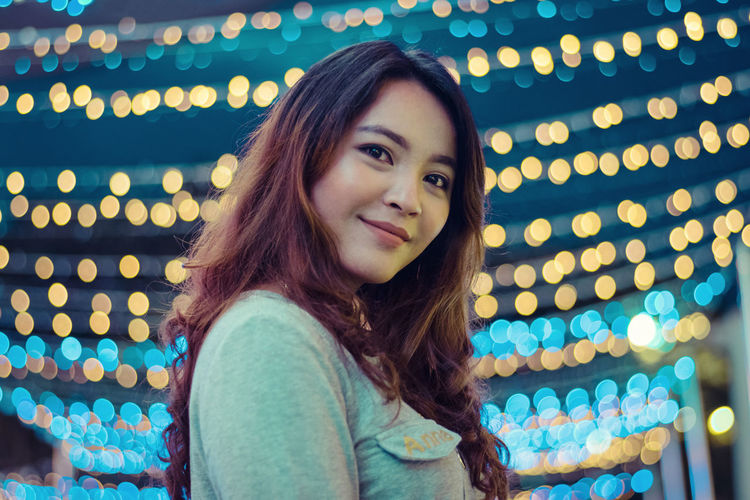 Close-up portrait of young woman amidst illuminated lights