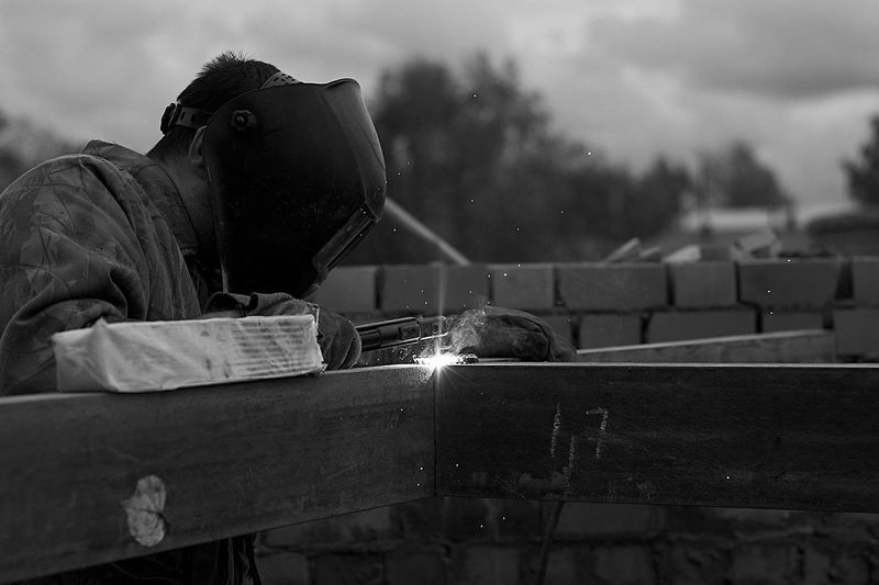 Man welding while standing against sky