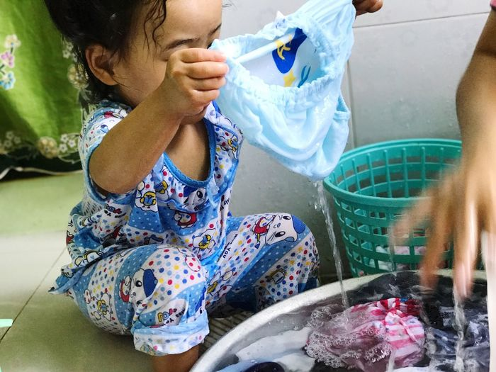 Little girl washing clothes and play water,enjoy activities of home, Can you be use copy space your text and concept design about children,activities of homework, family.