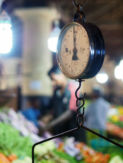 Close-up of weight scale hanging in market