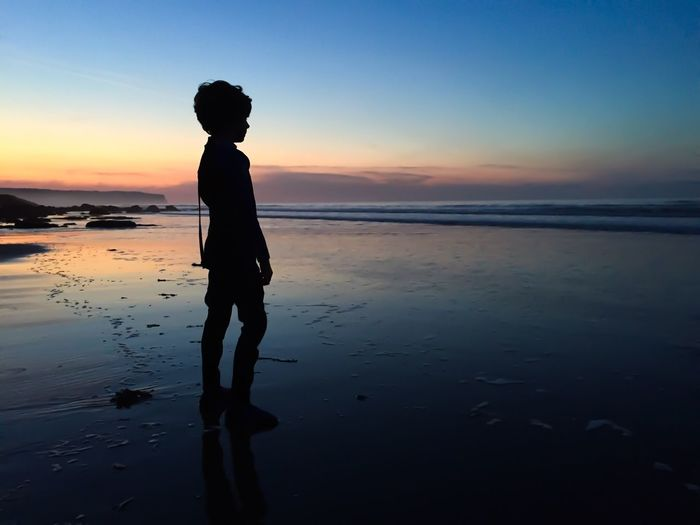 Silhouette Boy Standing On Shore Against Sky During Sunset