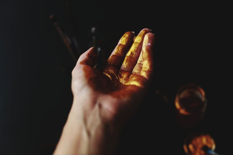 Cropped hand with golden paint