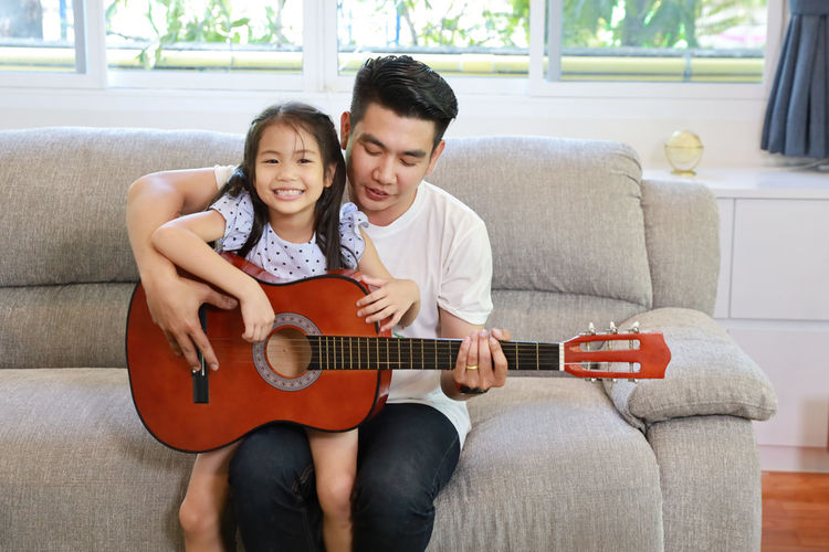 Father and daughter playing guitar at home