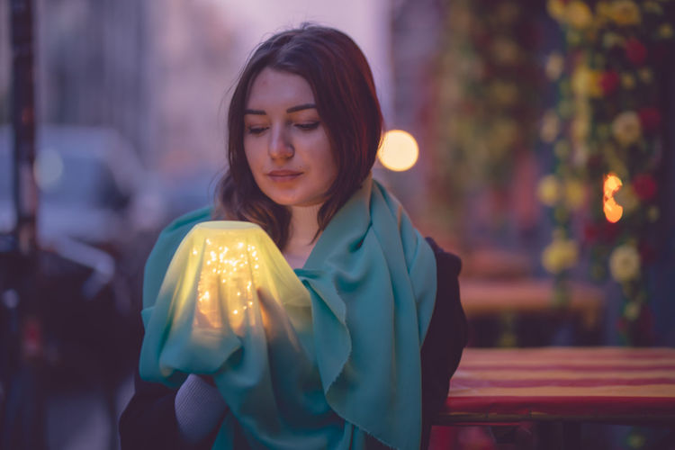 Beautiful woman holding glowing jar under blue scarf in city at dusk