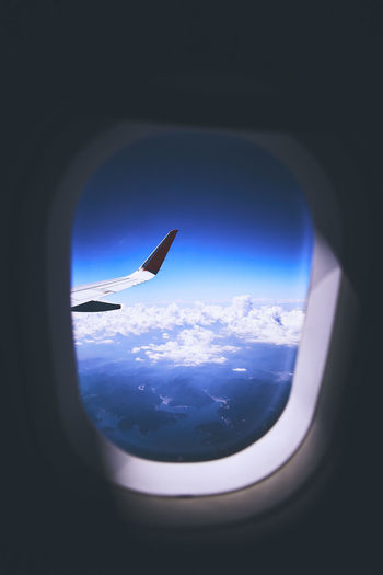 Airplane flying in sky seen through window