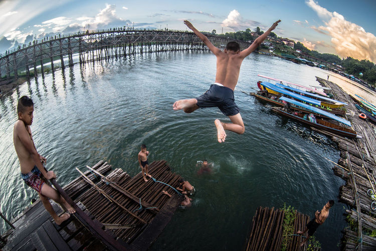 Capture Tomorrow Water Jumping Men Full Length Nature Mid-air Leisure Activity Enjoyment Group Of People Real People Day People Adult Fun Shirtless Motion Togetherness Sky Women Outdoors Human Arm