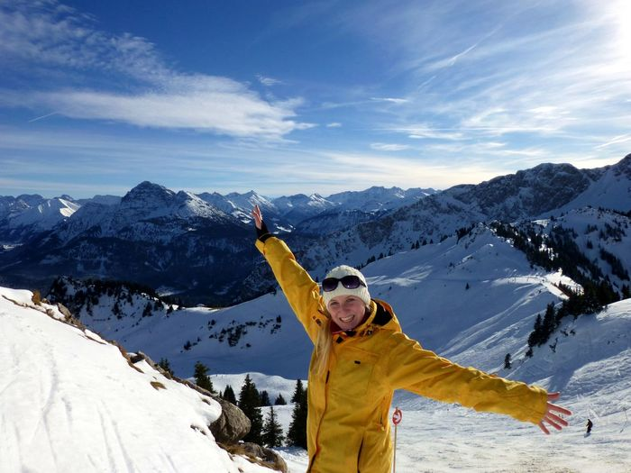 Woman with umbrella on snowcapped mountain against sky
