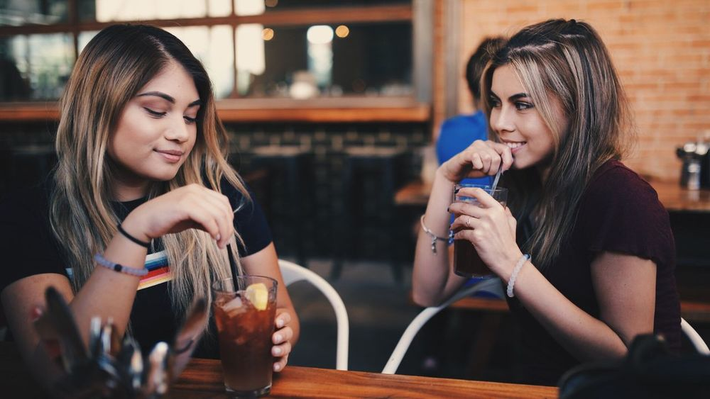 Leisure Activity Lifestyles Casual Clothing Sitting Friendship Focus On Foreground Person Togetherness Indoors  Young Women Young Adult Long Hair Looking Looking At Camera Day