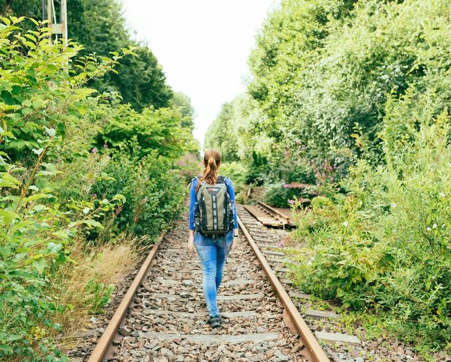 Rear view of woman walking on abandoned railroad track amidst plants