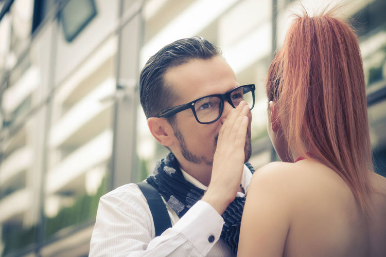 Close-up of man whispering to girlfriend against building in city