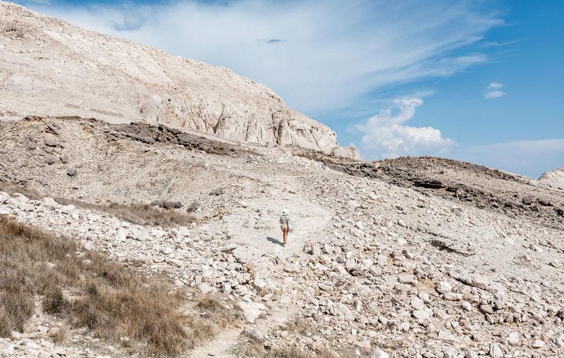 Rear view of tiny human walking on rocky path through arid terrain in summer.