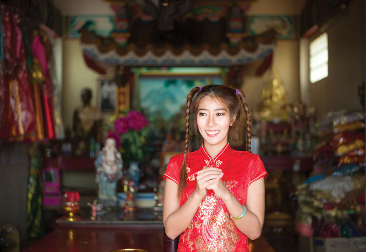 Smiling Young Woman In Traditional Clothing Standing At Home
