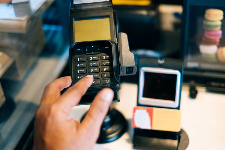 Cropped hand using credit card reader in store