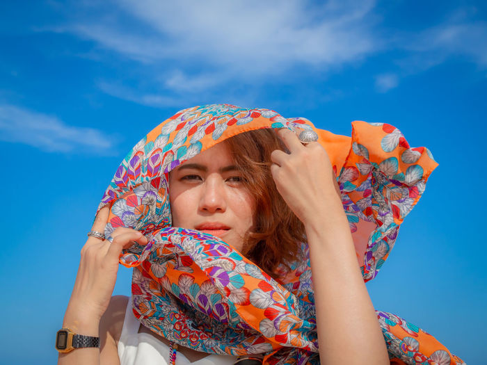 Portrait Of Woman With Scarf Against Sky