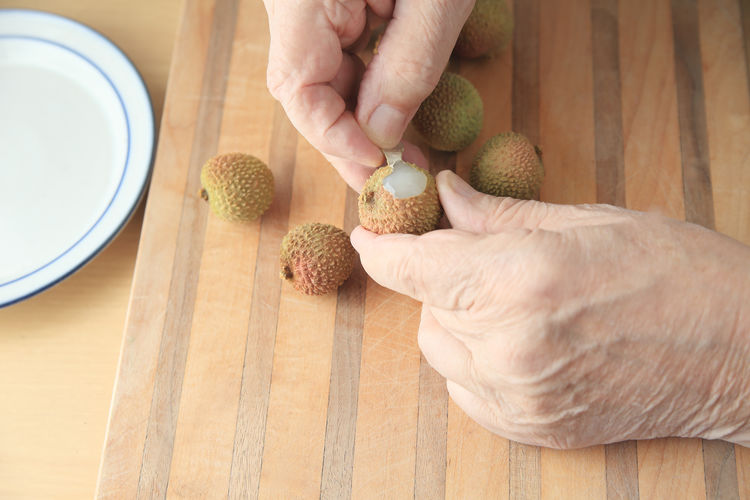 Cropped hands peeling lychee on table