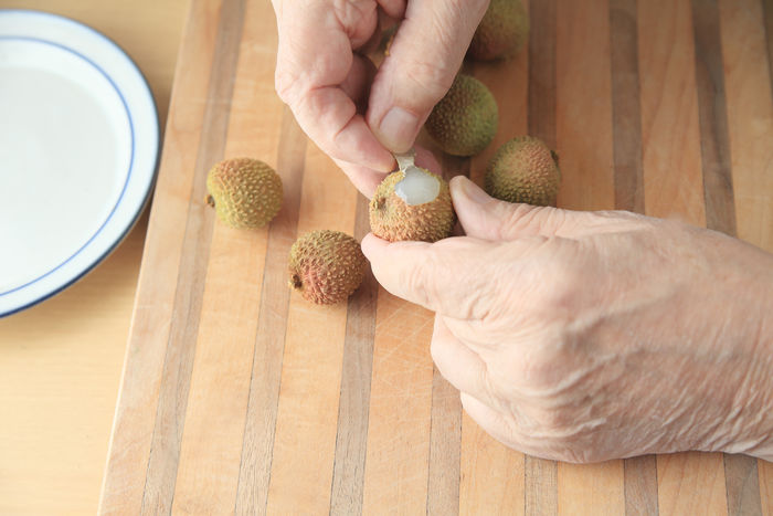 Peeling a fresh lychee fruit Close-up Cutting Board Cutting Boards Dish Exotic Fruit Fingers Food Food Preparation Fresh Fruit Freshness Hands Healthy Eating Holding Indoors  Natural Light One Person Overhead Peeling Text Space Wood Surface Wrinkled Skin