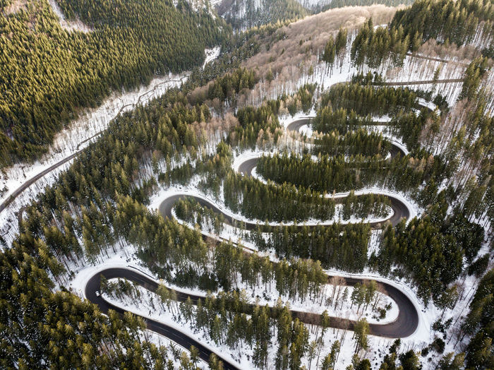 Winding road from high mountain pass, in winter time. Aerial view by drone . Romania Landscape Winter Drone  Dronephotography Aerial View Bird View Winding Road Fog Forest Wood Tree Journey