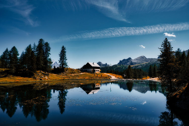 Reflection of trees and mountain shelter in lake against sky. lago federa