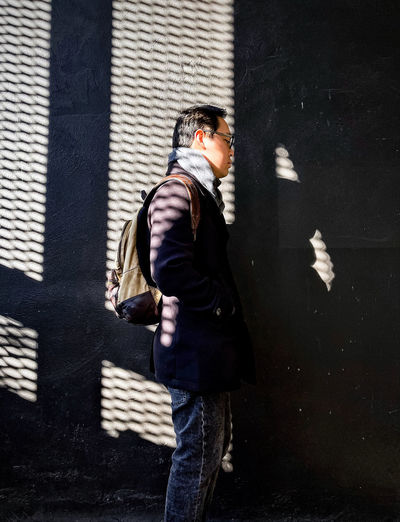 Side view of man standing against wall in city