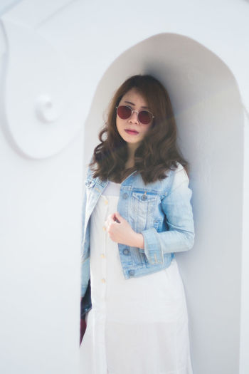 Young woman wearing sunglasses standing against white wall