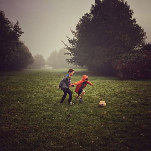 Full Length Of Siblings Playing Soccer On Grassy Field During Foggy Weather