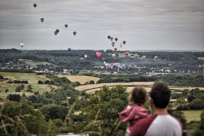 Rear view of father and daughter looking at hot air balloons during bristol international balloon fiesta