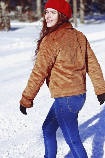 Winter, 2019 Winter Snow Cold Temperature Warm Clothing One Person Clothing Lifestyles Real People Leisure Activity Happiness Day Smiling Young Adult Standing Young Women Nature Front View Three Quarter Length Hat Outdoors Jeans Scarf Teenager Smile Happiness