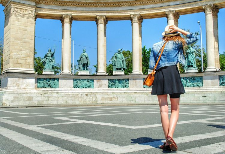 Woman walking against columned structure