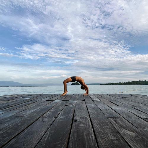 Full length of man on pier over sea against sky