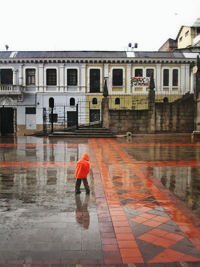 Traveling Home For The Holidays Wet Rain Water Lifestyles Walking Red Building Exterior Outdoors Architecture Built Structure Rainy Season Full Length City One Person People Day Quito Ecuador Reflection Cobblestone Streets One Boy Only Street Photography Coat Fashion