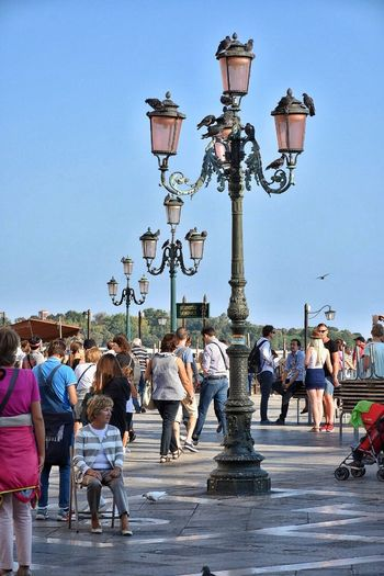 Street Light Lighting Equipment Clear Sky Large Group Of People Lifestyles Leisure Activity Person Blue City Electric Light Bridge - Man Made Structure Lamp Post City Life Casual Clothing Creativity Footpath Lamppost Venice People Piazza San Marco Tourism
