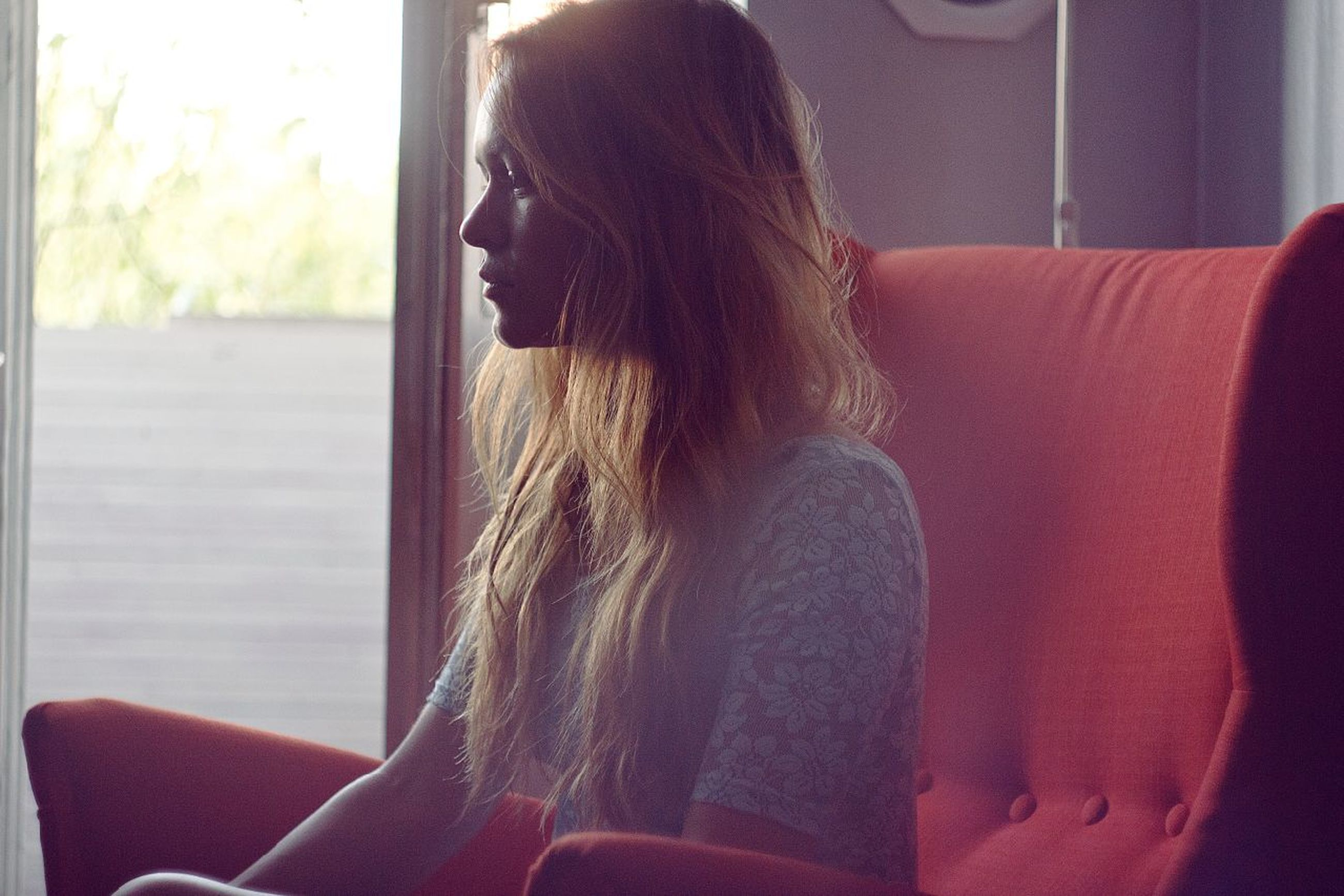 indoors, lifestyles, young adult, young women, long hair, leisure activity, person, waist up, window, home interior, casual clothing, headshot, sitting, side view, contemplation, rear view