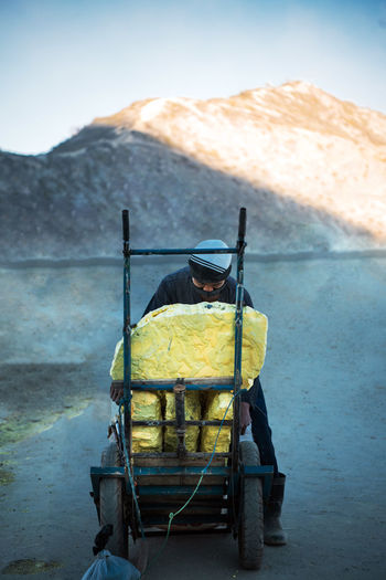 Man standing by rock in cart against mountain
