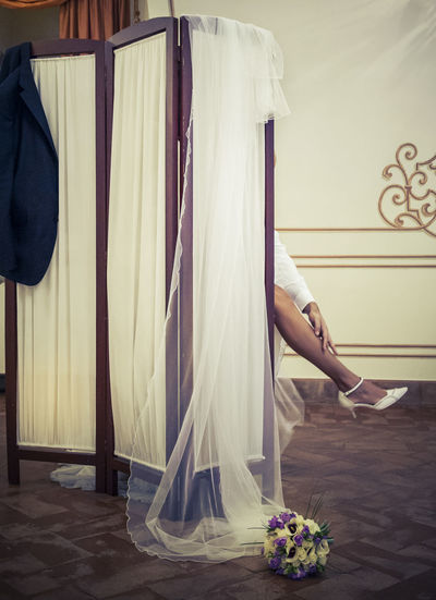Low section of bride behind screen partition in room