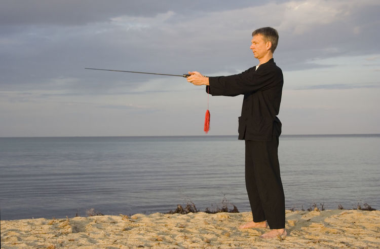 tai chi - posture the compass - art of self-defense Beach Chinese Culture Fitness Healthy Lifestyle Holding Man Martial Arts Mature Men Men One Man Only One Mature Man Only One Person People Sea Self-Defense Forces Selfdefense Sports Clothing Sword Tai Chi Tai Chi Chuan Taiji Taijiquan Training Water Weapon