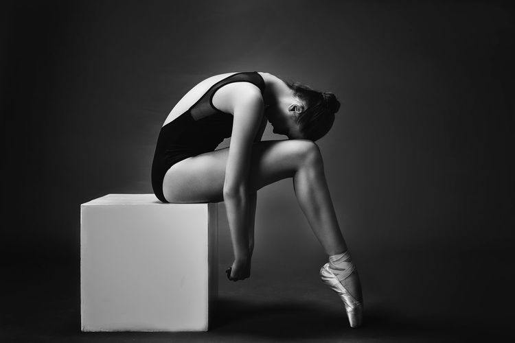 Side view ballet dancer sitting on box against gray background