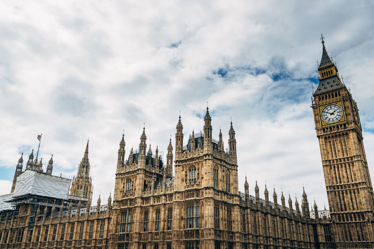 Low angle view of big ben and houses of parliament against cloudy sky