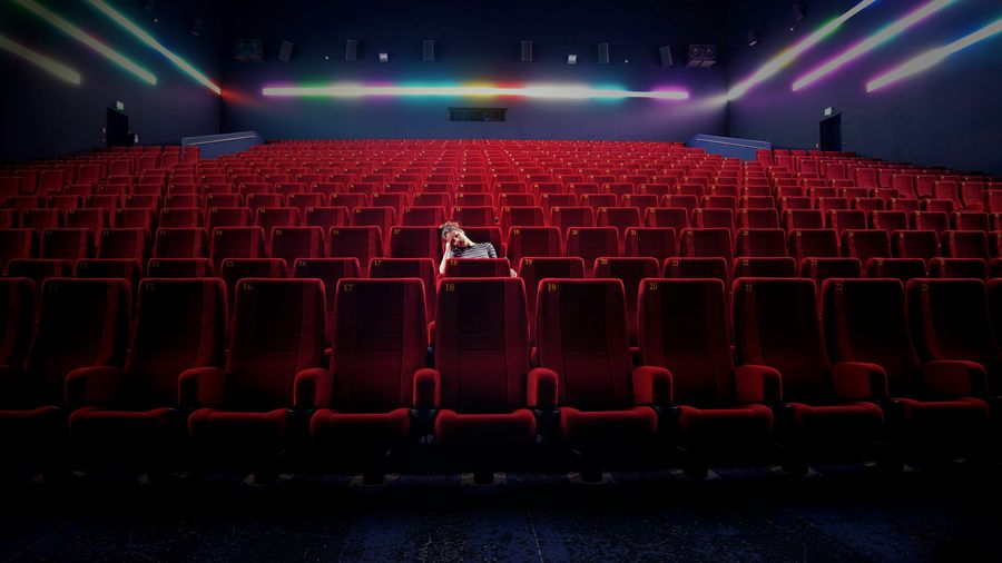 Depressed woman sitting in alone at movie theater