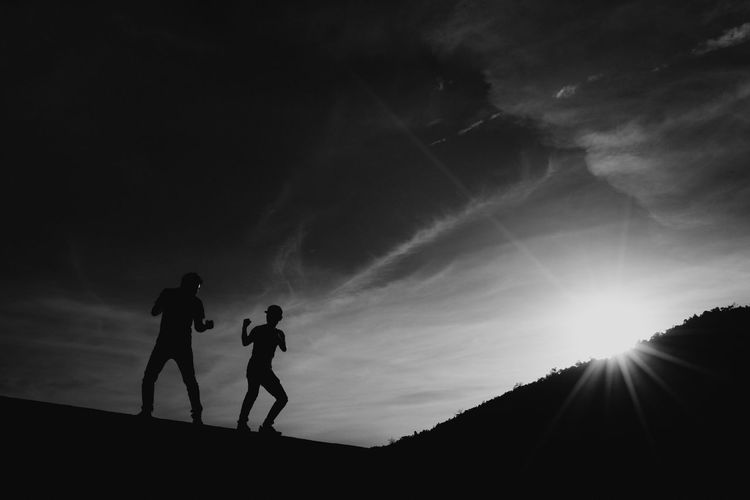 Low Angle View Of Silhouette Friends Playing On Field Against Sky