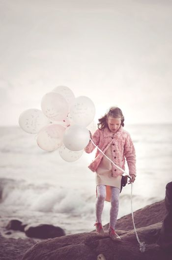 Full Length Of Girl With Helium Balloons Walking On Rock At Beach Against Sky