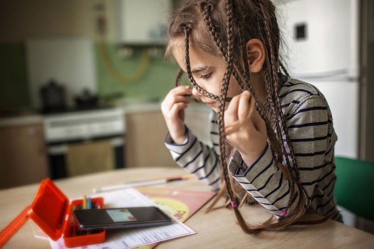 Pretty stylish schoolgirl studying math during her online lesson at home, online education concept