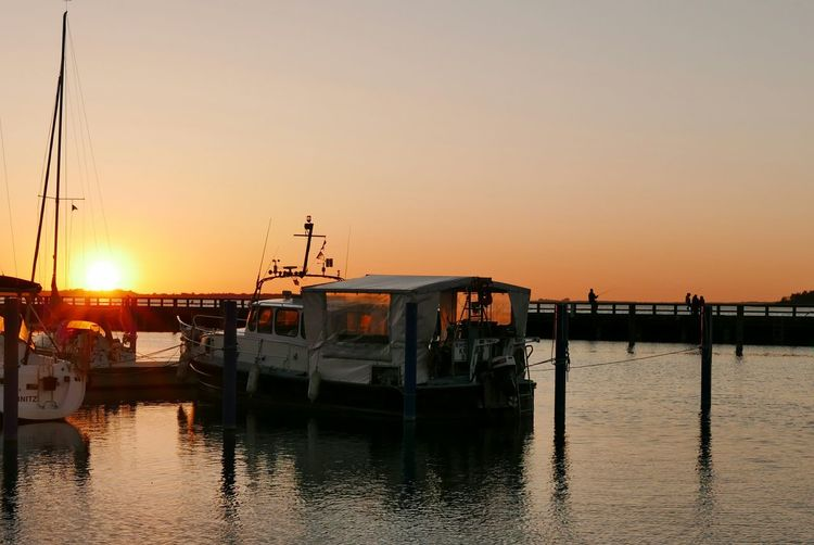 Boats moored at harbor against clear sky during sunset