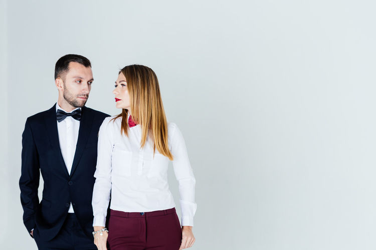 Elegant man looking at thoughtful woman against blue background