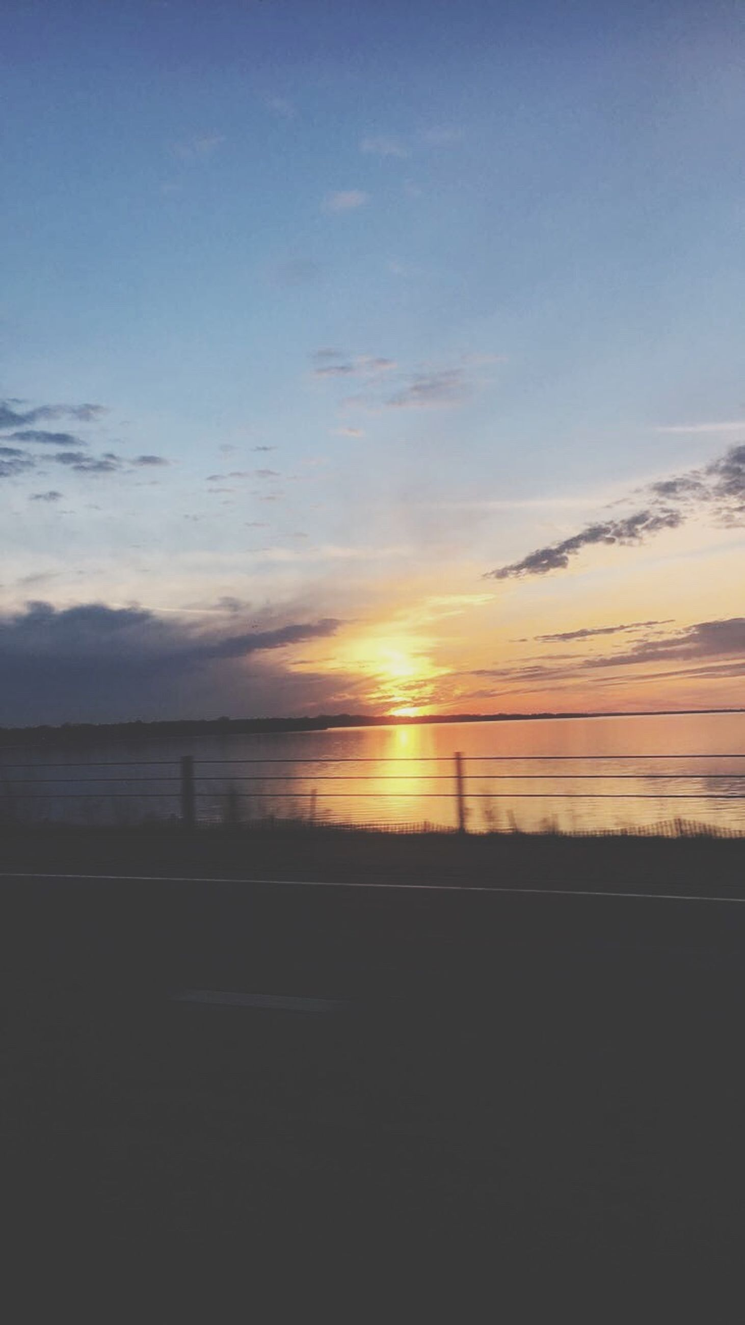 sunset, scenics, sea, beauty in nature, tranquil scene, tranquility, water, nature, beach, sky, outdoors, horizon over water, no people, road, cloud - sky, day