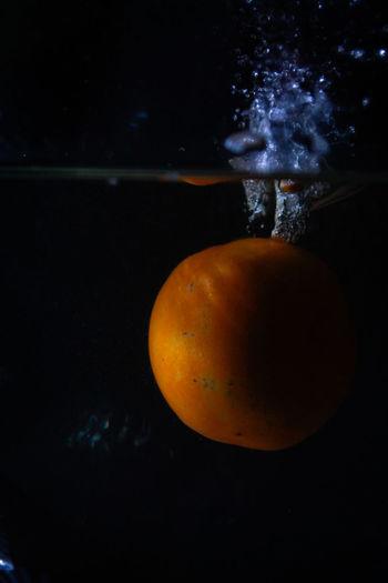 Close-up of orange apple against black background